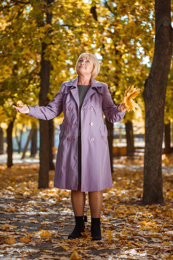 Una mujer de mediana edad atractiva que camina en un parque del otoño en un fondo borroso imagenes de archivo
