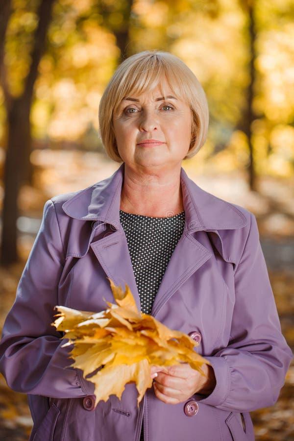 Una mujer de mediana edad atractiva que camina en un parque del otoño en un fondo borroso fotos de archivo libres de regalías