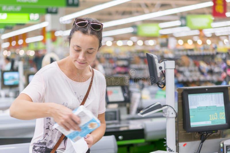 Una mujer de mediana edad en el pago y envío en el supermercado La mujer cuenta en el pago y envío en el supermercado imagenes de archivo