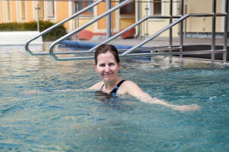 Una mujer de mediana edad está nadando en los baños imagen de archivo