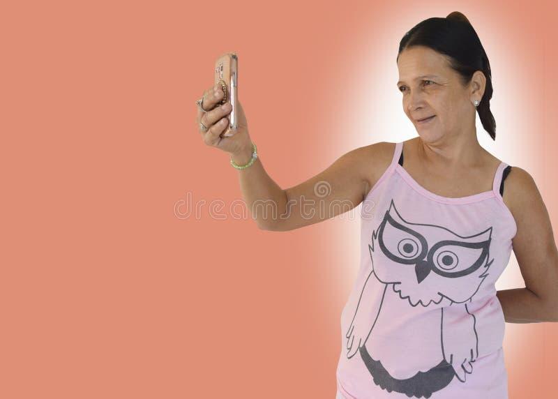 Una mujer de mediana edad que sonríe y que toma un selfie usando su teléfono androide fotografía de archivo libre de regalías