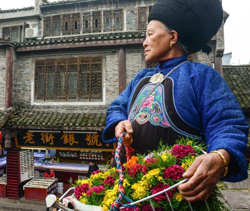 Una mujer de Miao que vende las flores en la ciudad antigua de Fenghuang en Hunan, China fotografía de archivo libre de regalías