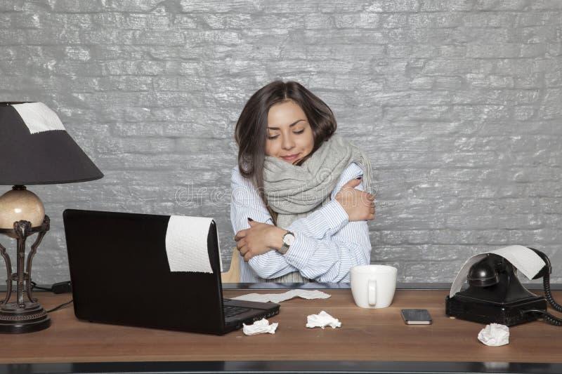 Una mujer de negocios enferma está sacudiendo con frío y trabajo excesivo imagen de archivo