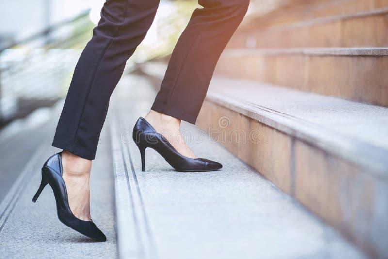 Una mujer de negocios moderna que trabaja cierra las piernas caminando por las escaleras en la ciudad moderna en hora punta para t fotografía de archivo