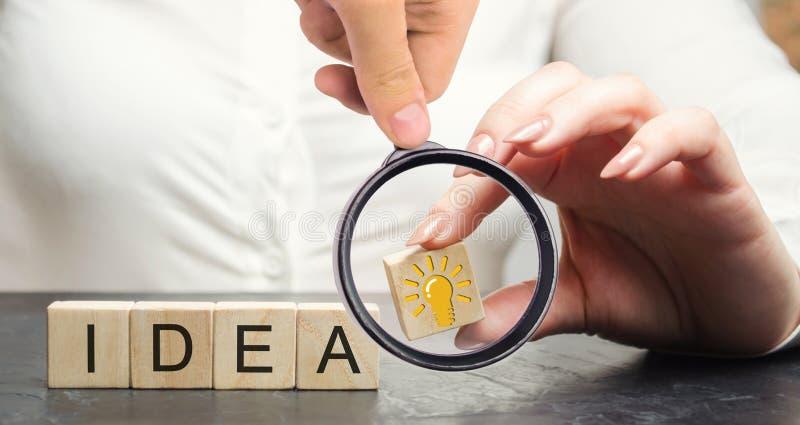 Una mujer de negocios que lleva a cabo un bloque de madera con una idea o una inspiración de la bombilla Generación de ideas inno foto de archivo libre de regalías