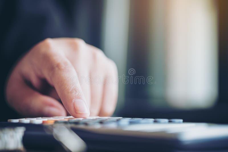 Una mujer de negocios que usa la calculadora en oficina imagenes de archivo