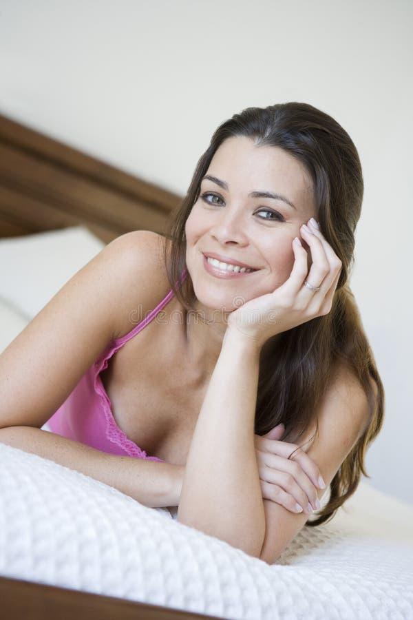 Una mujer de Oriente Medio que miente en una cama foto de archivo libre de regalías