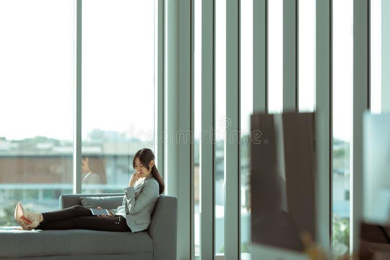 Una mujer de pelo largo asiática está asistiendo en la sensación del sofá sola imágenes de archivo libres de regalías
