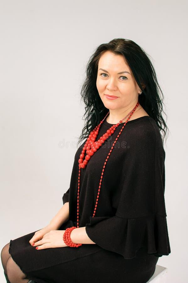 Una mujer de pelo oscuro hermosa toca su pelo Un retrato grande La visten en un vestido negro Ella tiene étnico rojo imagen de archivo libre de regalías