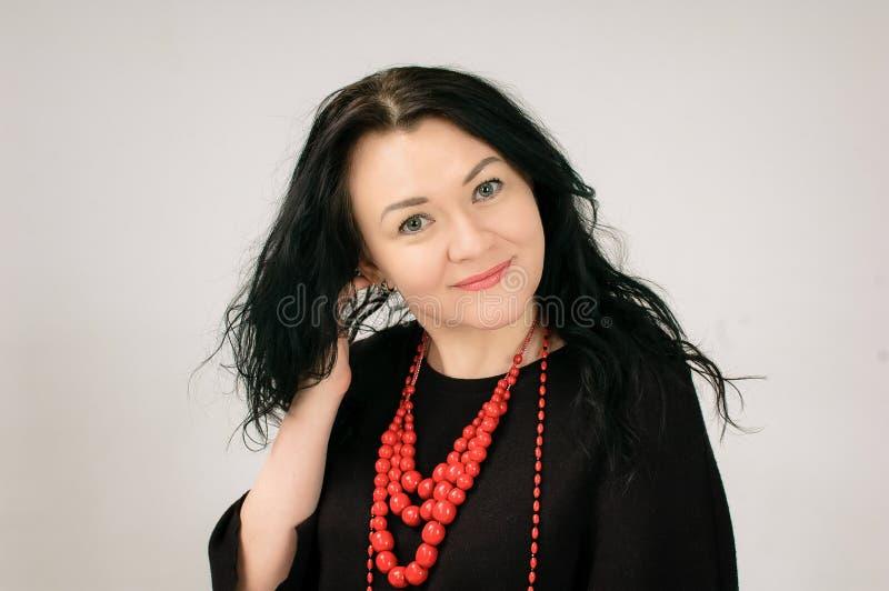 Una mujer de pelo oscuro hermosa toca su pelo Un retrato grande La visten en un vestido negro Ella tiene étnico rojo imagenes de archivo