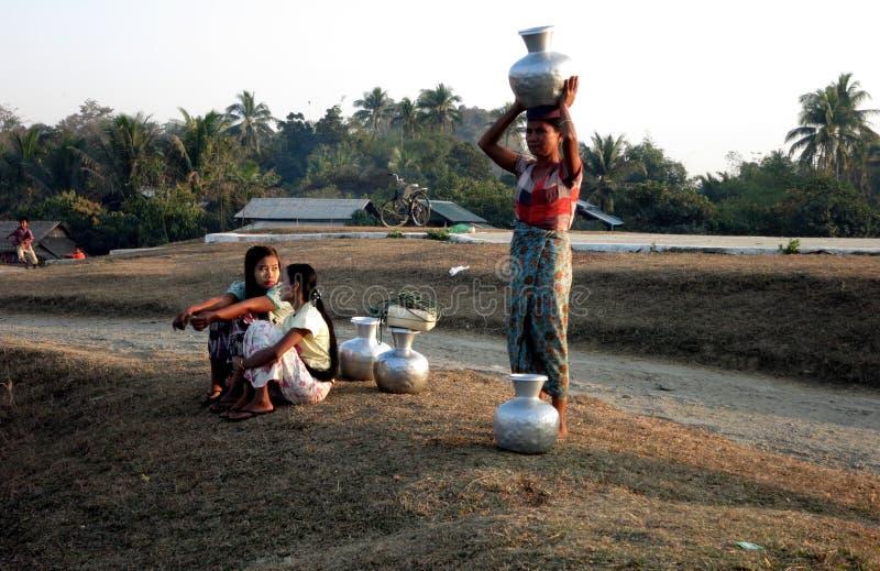 Una mujer del birmano que pone los tarros llenos de agua en su cabeza imagen de archivo libre de regalías