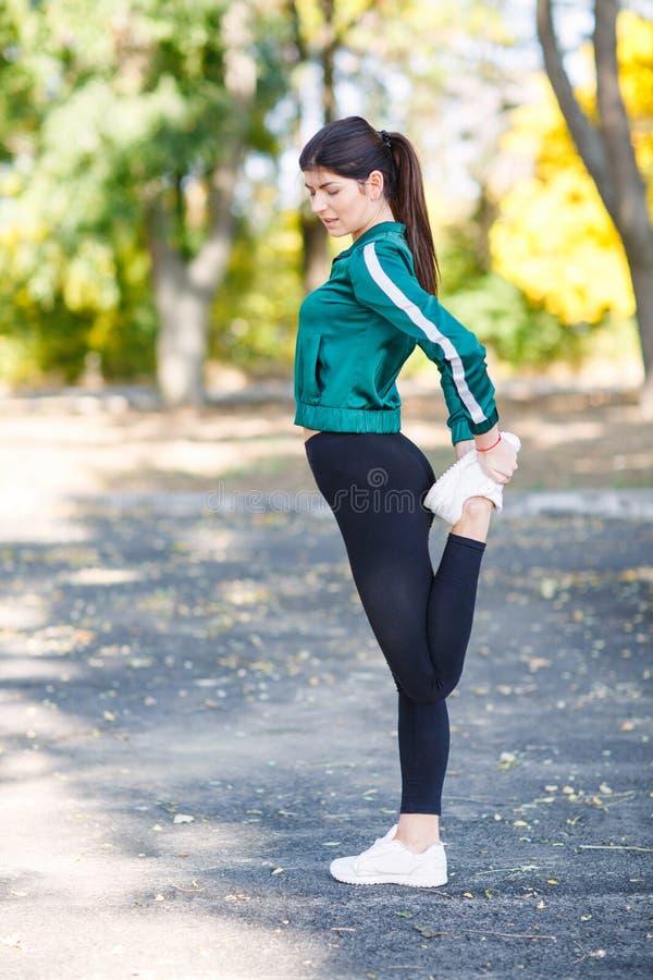 Una mujer deportiva joven con el cuerpo perfecto que hace los ejercicios al aire libre foto de archivo libre de regalías