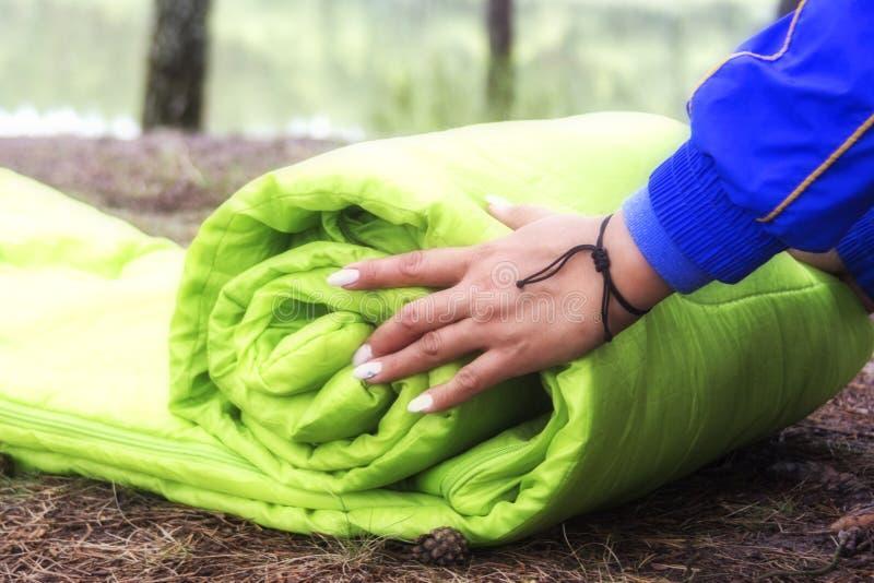 Una mujer dobla y embala un saco de dormir, pasando en un viaje a través del bosque el concepto de turismo y de turismo ecológico foto de archivo libre de regalías