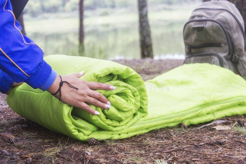 Una mujer dobla y embala un saco de dormir, pasando en un viaje a través del bosque el concepto de turismo y de turismo ecológico fotos de archivo