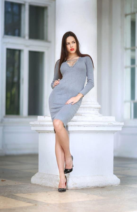 Una mujer elegante en el fondo de ventanas La señora preety en un vestido gris al aire libre La muchacha que presenta antes del b fotos de archivo