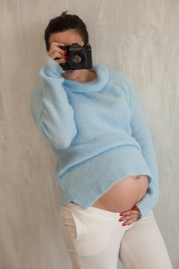 Una mujer embarazada con los géneros morenos de un retrato de la cámara agradables foto de archivo