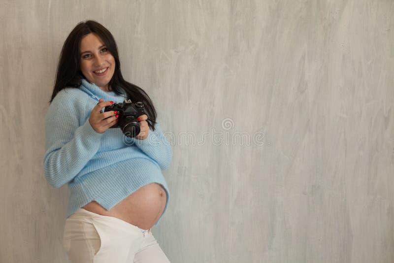 Una mujer embarazada con los géneros morenos de un retrato de la cámara agradables imagenes de archivo