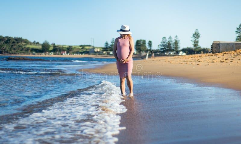 Una mujer embarazada en el vestido rosado que se sostiene el vientre y que camina encendido imagen de archivo