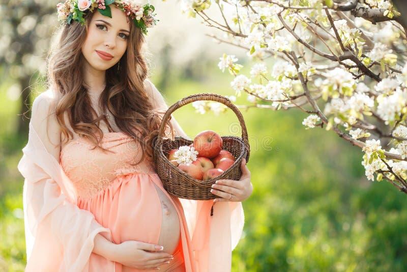 Una mujer embarazada en un jardín de la primavera con la cesta imágenes de archivo libres de regalías