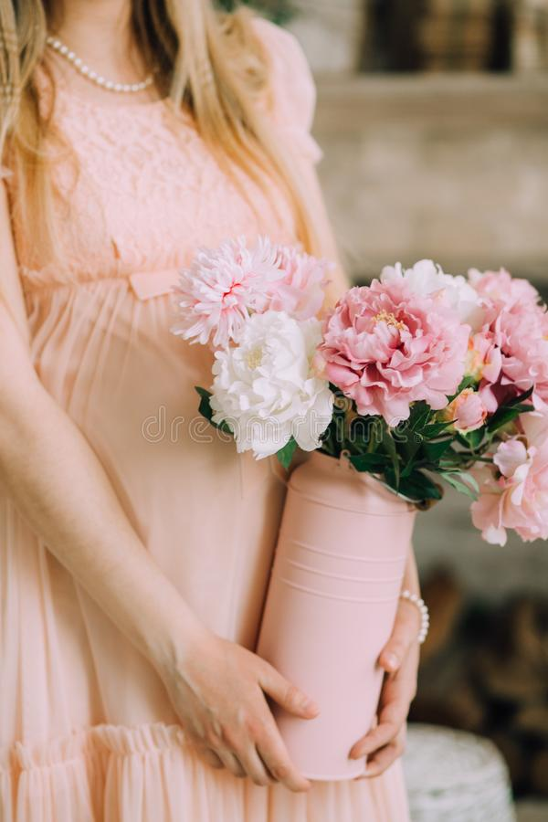 Una mujer embarazada en un vestido rosado delicado sostiene un florero de peonías con sus manos imagenes de archivo