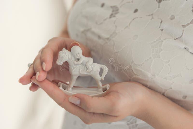 Una mujer embarazada está llevando a cabo una pequeña figura de un caballo y de un chil imágenes de archivo libres de regalías