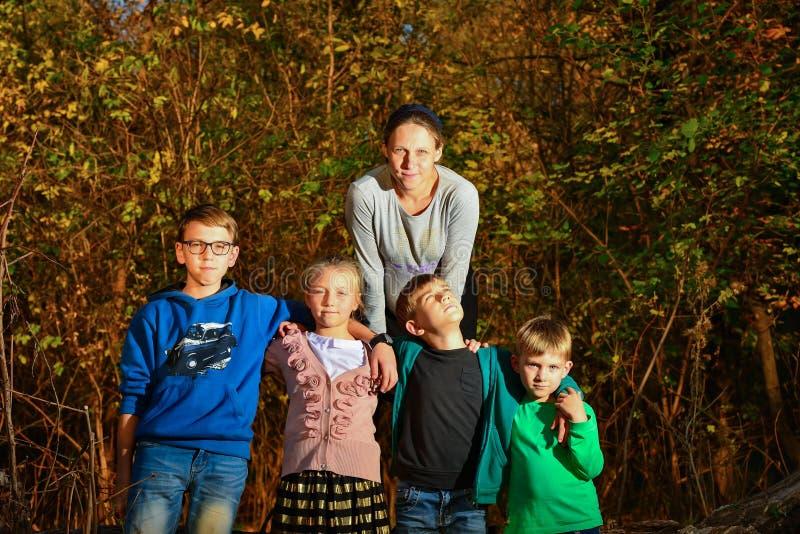 Una mujer embarazada se coloca en un bosque en un árbol, y cuatro niños están en el parque al lado de su madre Madre de muchos ni imagen de archivo
