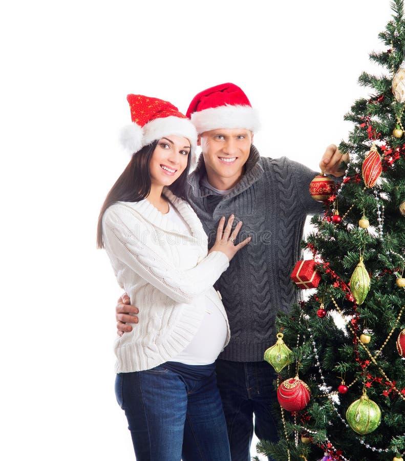 Una mujer embarazada y un hombre que celebran la Navidad foto de archivo libre de regalías