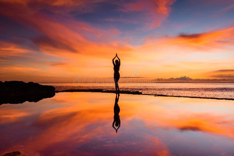 Una mujer en una actitud de la yoga silueteada contra una puesta del sol con su reflexión en el agua imagen de archivo