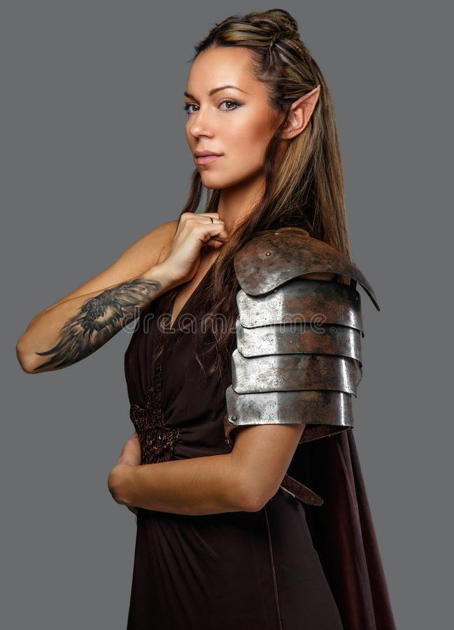 Una mujer en armadura con el tatuaje en su mano foto de archivo