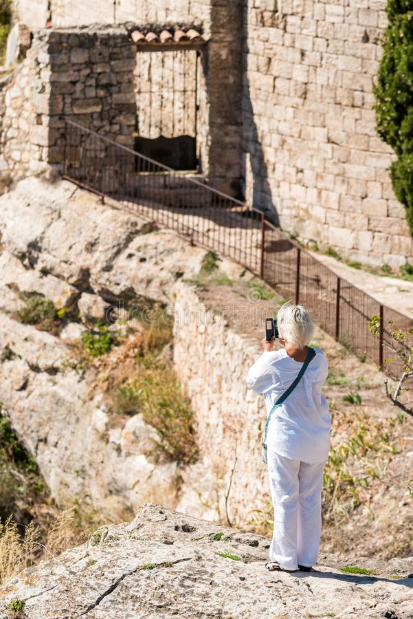 Una mujer en blanco en un acantilado en el Siurana, Tarragona, Catalunya, España Visión posterior vertical fotografía de archivo libre de regalías