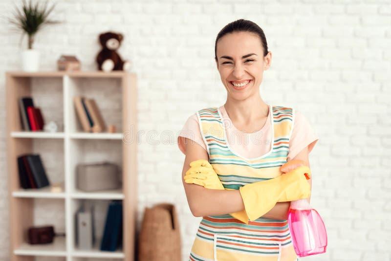 Una mujer en una camiseta blanca que presenta en casa con los fondos para limpiar la casa imagen de archivo libre de regalías
