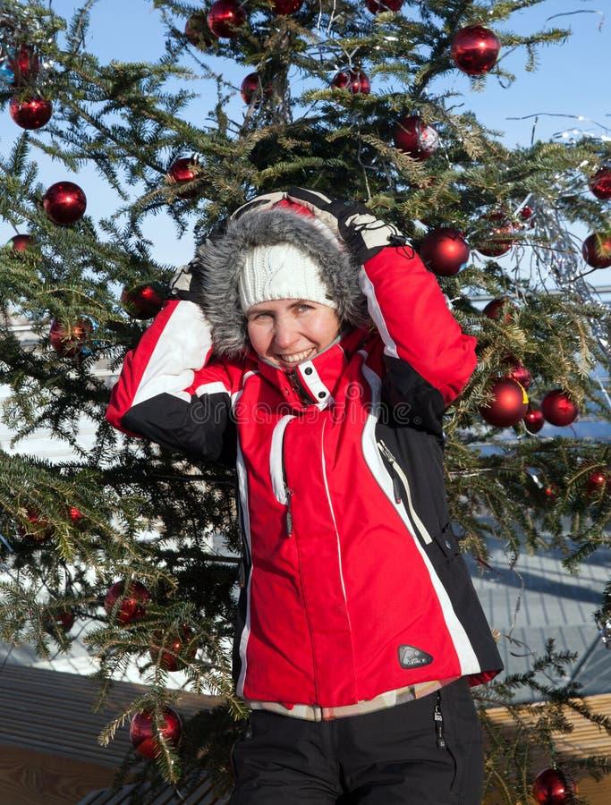 Una mujer en chaqueta de esquí en el árbol de navidad imagen de archivo
