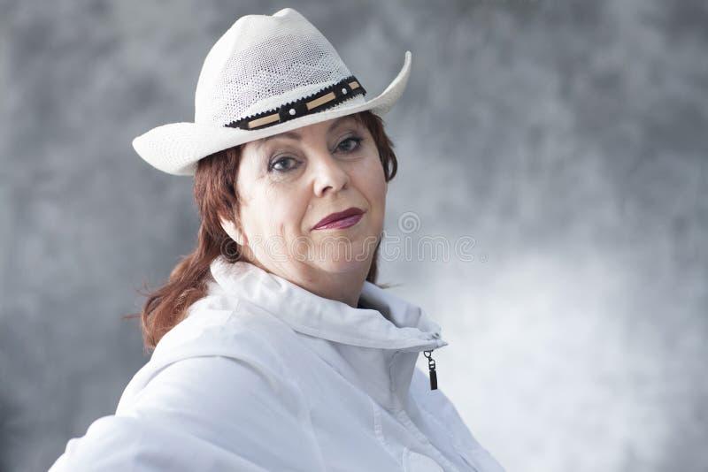 Una mujer en una chaqueta y un sombrero del ` s del hombre foto de archivo
