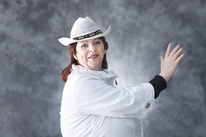 Una mujer en una chaqueta y un sombrero del ` s del hombre imagen de archivo