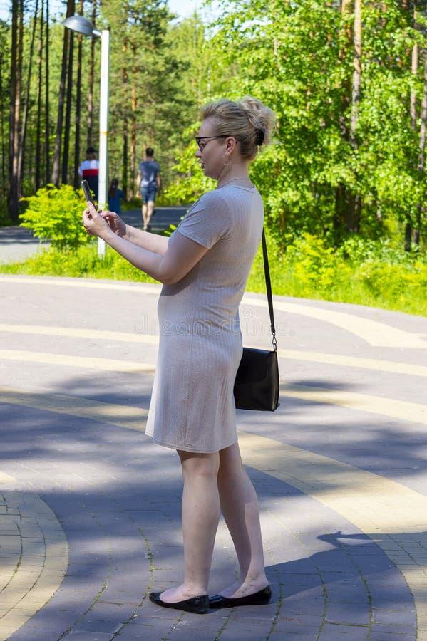Una mujer en el parque está tomando imágenes en un smartphone foto de archivo libre de regalías