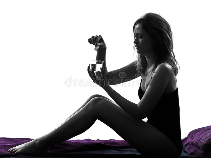 Mujer que toma la medicina efervescente en silueta de la cama imagen de archivo