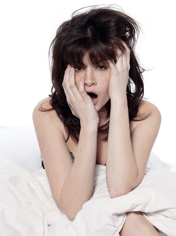 Una mujer en la cama que despierta insomnio cansado de bostezo fotos de archivo libres de regalías
