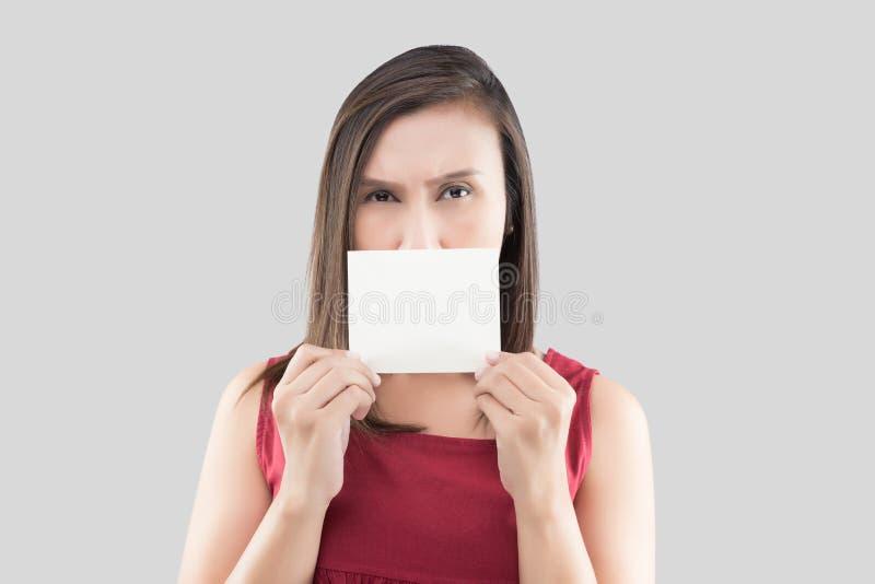Una mujer en la camisa roja que sostiene la tarjeta blanca en blanco con el espacio para el texto delante de su boca contra el fo fotos de archivo libres de regalías