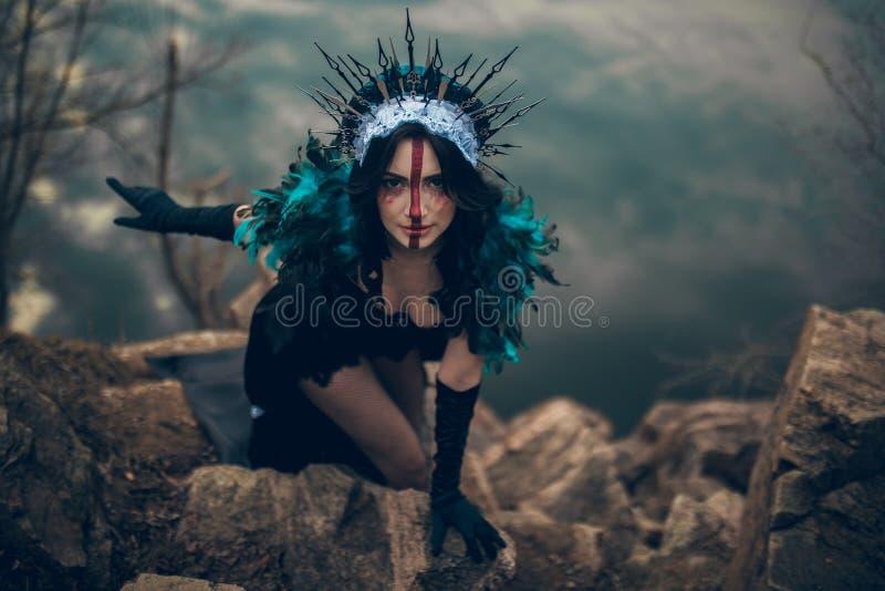 Una mujer en la imagen de una hada y una situación de la bruja sobre un lago en un vestido negro y una corona imagen de archivo libre de regalías