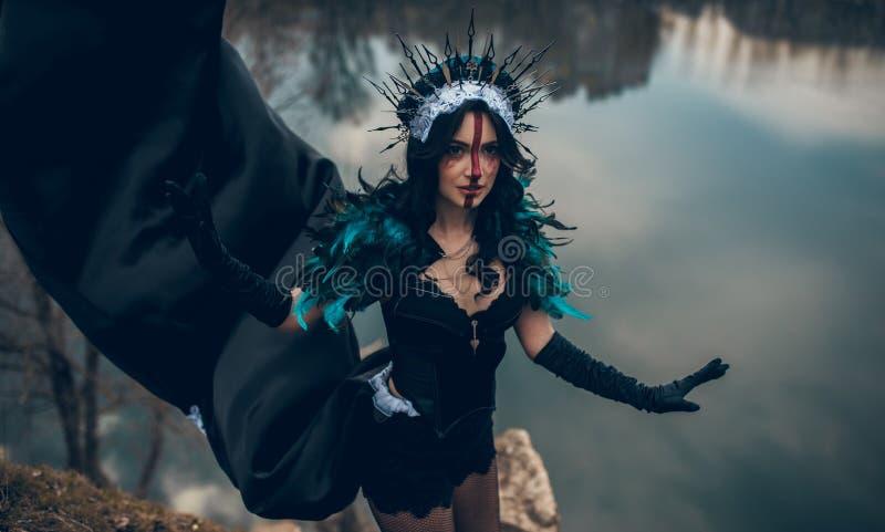 Una mujer en la imagen de una hada y una situación de la bruja sobre un lago en un vestido negro y una corona imagen de archivo