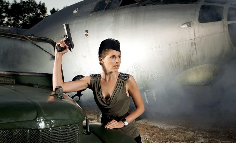 Una mujer en la ropa militar que presenta cerca de un avión imagen de archivo