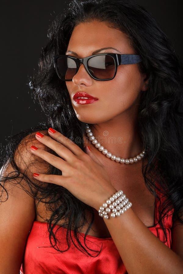 Una mujer en las gafas de sol que fuman un cigarro imagen de archivo