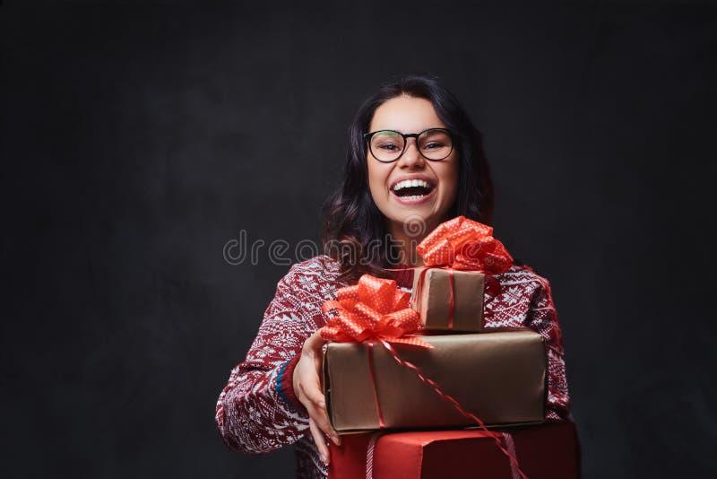 Una mujer en lentes sostiene los regalos de la Navidad imágenes de archivo libres de regalías