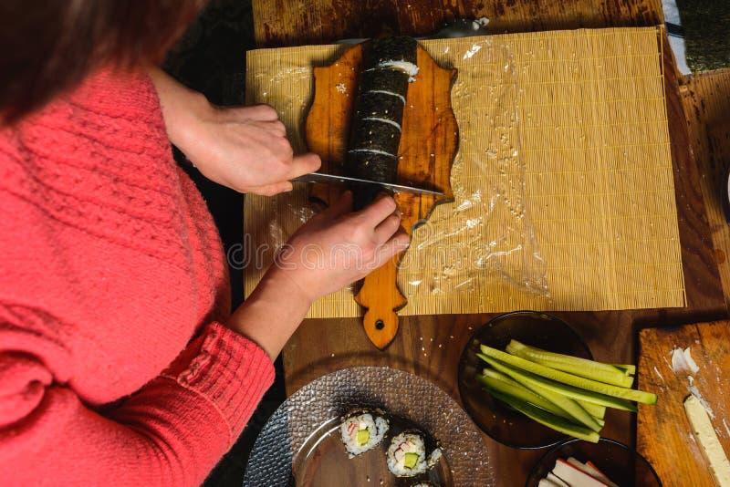 Una mujer en los cortes de la cocina el cuchillo con un rollo del sushi en el nivel de los pedazos para los visitantes fotos de archivo libres de regalías