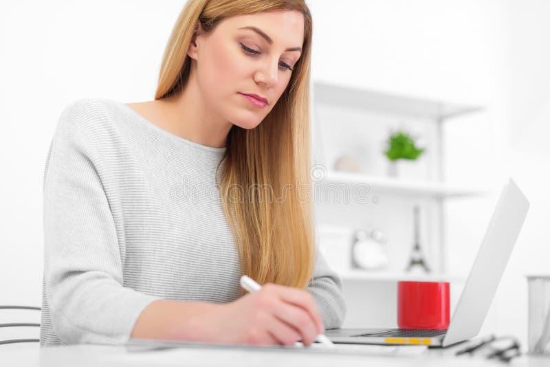 Una mujer en una oficina blanca se está sentando en una tabla y una escritura Una señora joven que usa un ordenador portátil llen fotografía de archivo libre de regalías