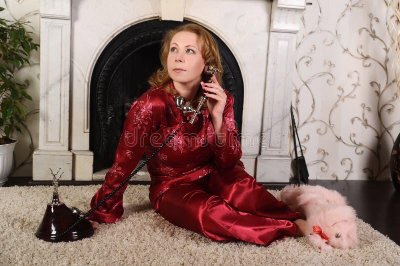 Una mujer en pijamas rojos se está sentando por la chimenea de mármol, hablando en un teléfono del vintage imagenes de archivo