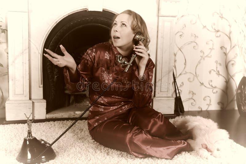 Una mujer en pijamas rojos se est? sentando por la chimenea de m?rmol, hablando en un tel?fono del vintage fotos de archivo