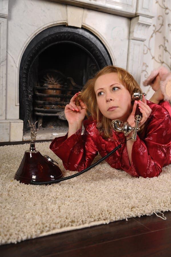 Una mujer en pijamas rojos se est? sentando por la chimenea de m?rmol, hablando en un tel?fono del vintage imagenes de archivo