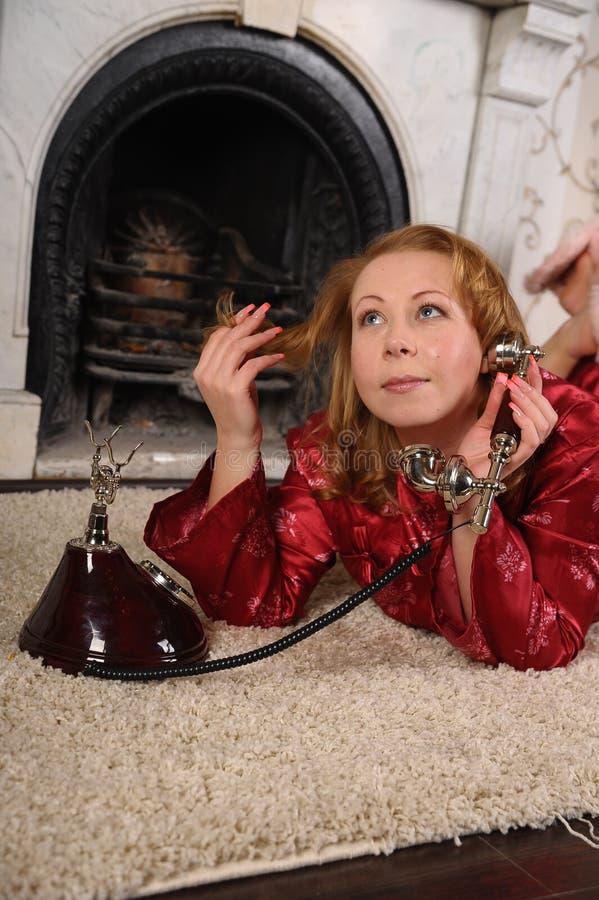 Una mujer en pijamas rojos se est? sentando por la chimenea de m?rmol, hablando en un tel?fono del vintage foto de archivo libre de regalías