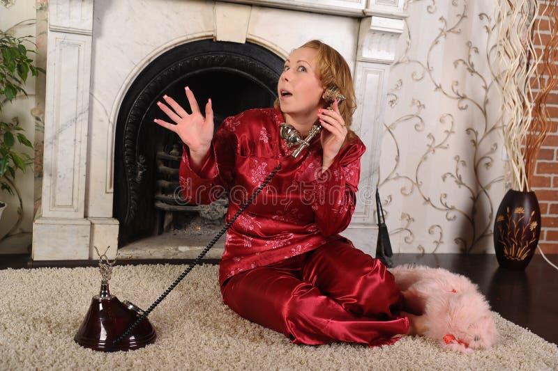 Una mujer en pijamas rojos se est? sentando por la chimenea de m?rmol, hablando en un tel?fono del vintage fotos de archivo libres de regalías